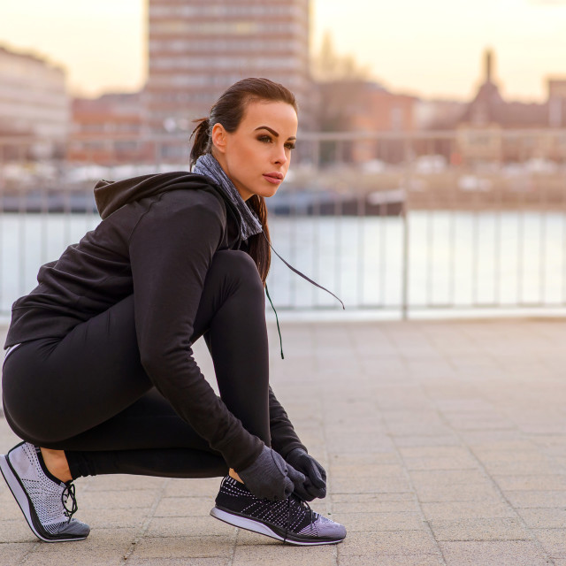"""""""A sporty young woman tying her shoelace"""" stock image"""