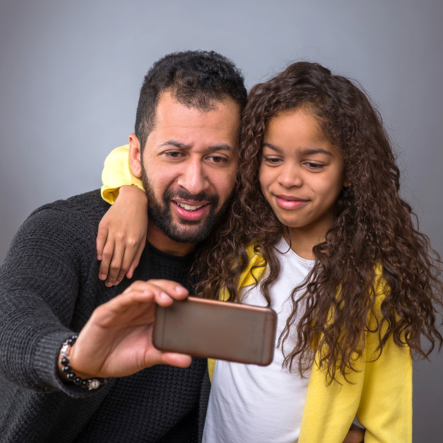 """""""Black father taking selfies with his daughter"""" stock image"""