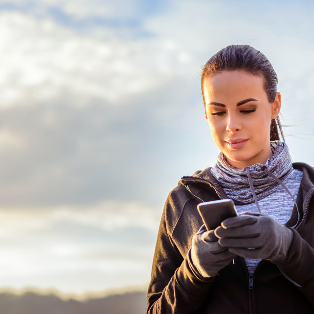 """""""Young sporty woman standing in the sunset with a mobile"""" stock image"""