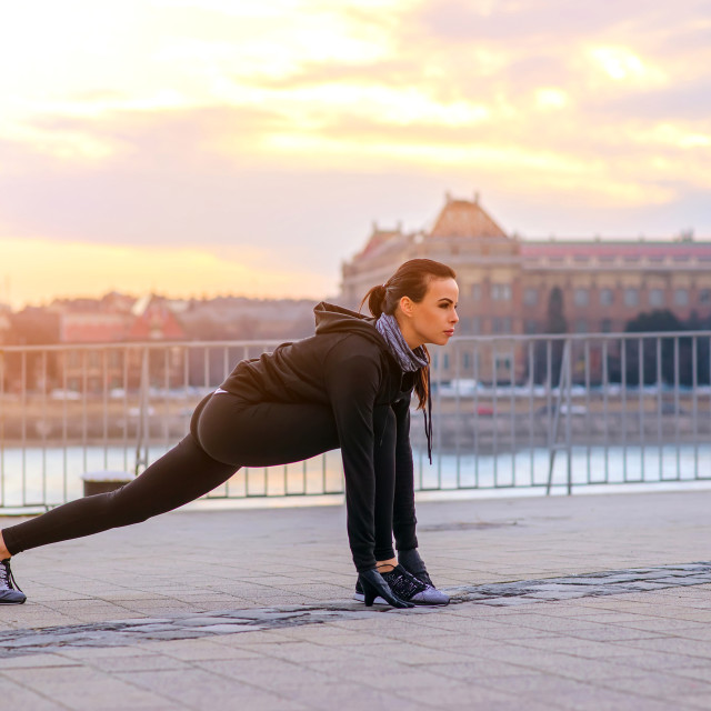 """""""A sporty young woman stretching in the sunset"""" stock image"""