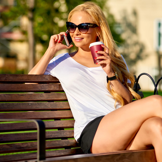 """""""Young woman siting on a bench and talking on her phone"""" stock image"""