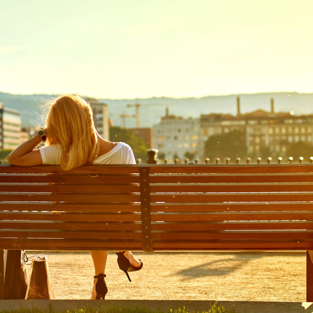 """""""Young woman siting on a bench on the riverside"""" stock image"""