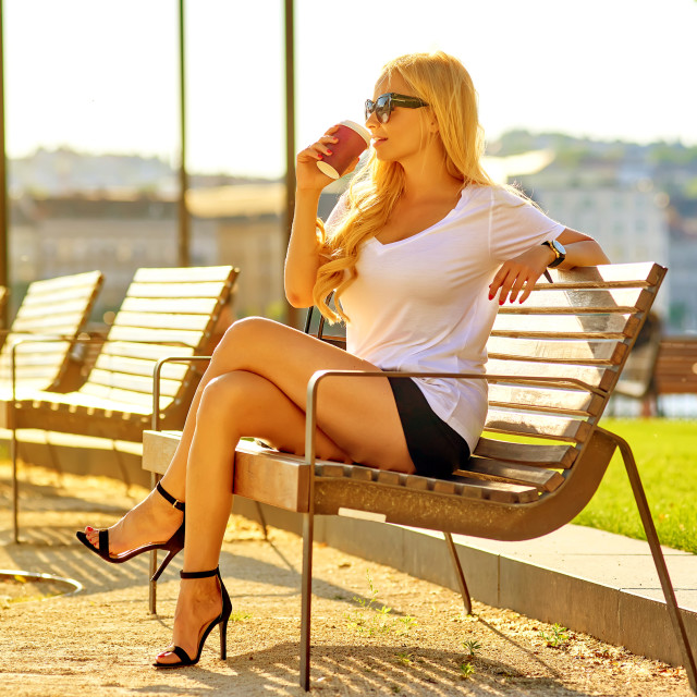 """""""Young woman siting on a bench with a coffee"""" stock image"""