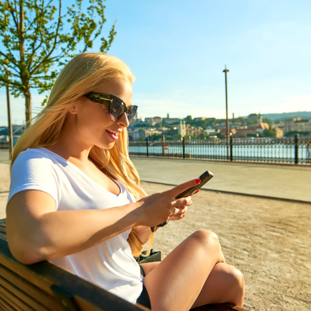 """""""Young woman siting on a bench and using her phone"""" stock image"""