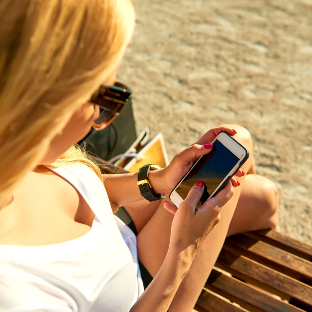 """""""Young woman on a bench and using her phone"""" stock image"""