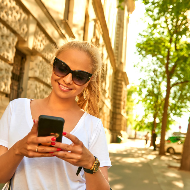 """""""Young woman using her phone on the street with bags"""" stock image"""