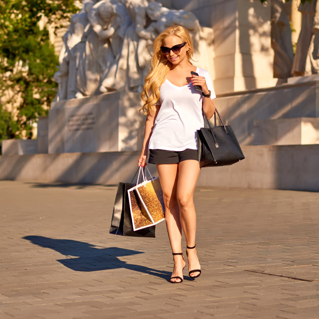"""""""Young woman walking with shopping bags in the sunset"""" stock image"""