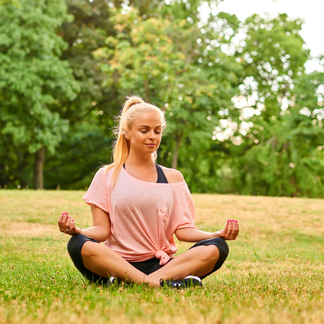 """""""Young woman meditating on a field in a park"""" stock image"""