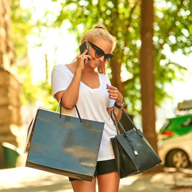 """""""Young woman talking on the phone on the street with bags"""" stock image"""