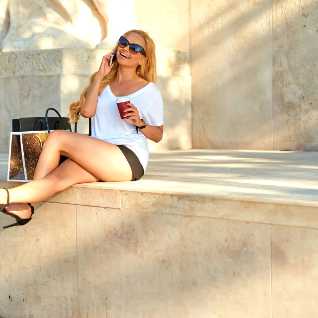 """""""Young woman siting and talking on her phone"""" stock image"""