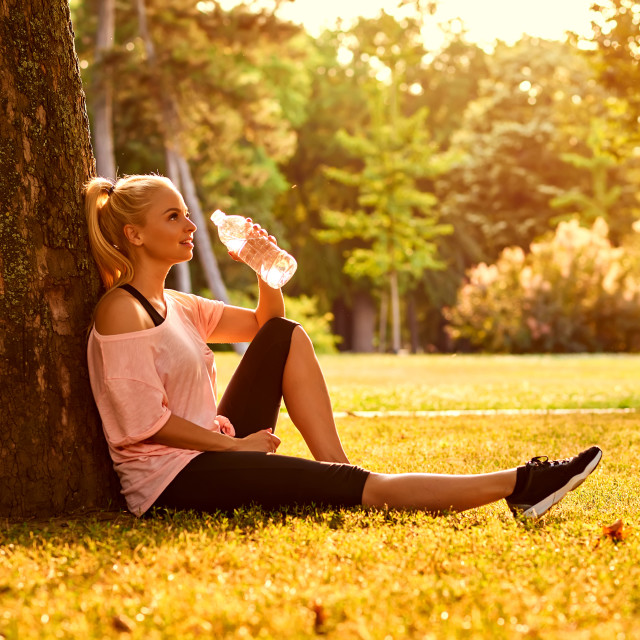 """""""Young woman sitting at a tree in a park and drinking water"""" stock image"""