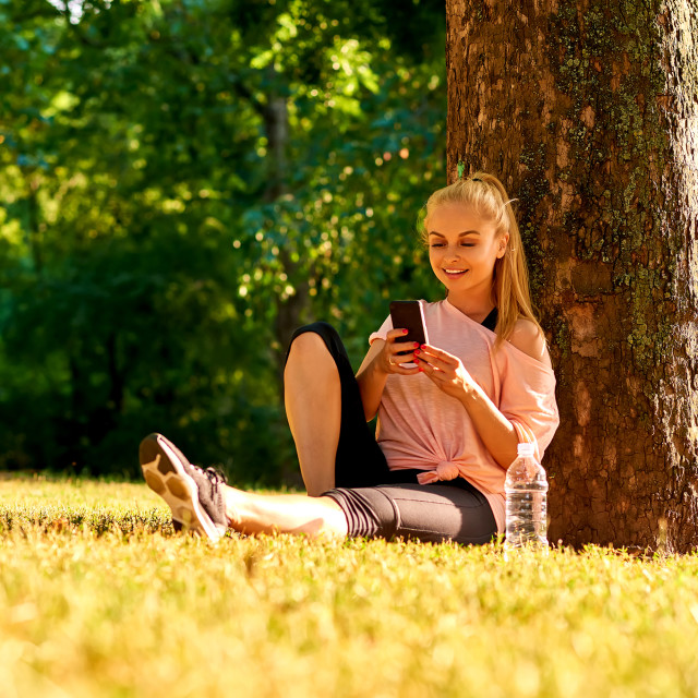"""""""Young woman sitting at a tree in a park with her phone"""" stock image"""