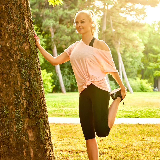 """""""Young woman stretching next to a tree in the sunset"""" stock image"""
