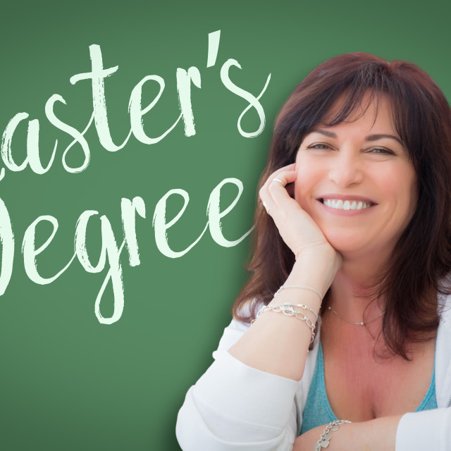 """""""Master's Degree Written On Green Chalkboard Behind Smiling Middle Aged Woman"""" stock image"""