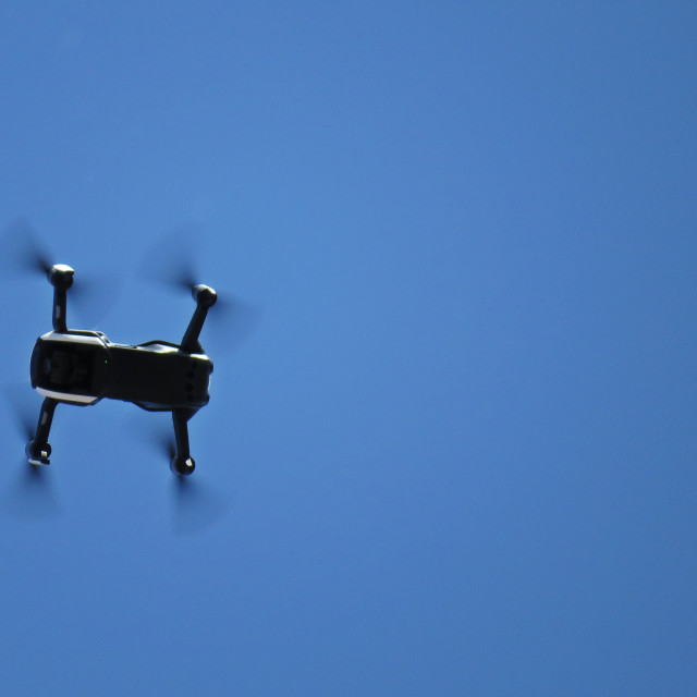 """Professional Drone with Four Propellers and Camera Flying with a Blue Sky in..."" stock image"