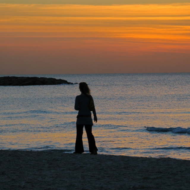 """A woman on the beach at sun set over the Mediterranean Sea, Isra"" stock image"