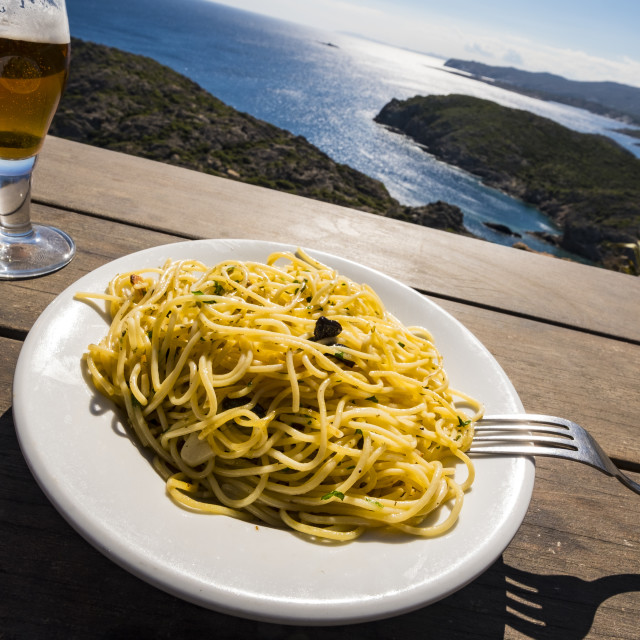 """""""Plate with spaghetti with the Costa Brava in the background and its small bays in the nature reserve of Cap de Creus in the province of Girona in Catalonia Spain"""" stock image"""