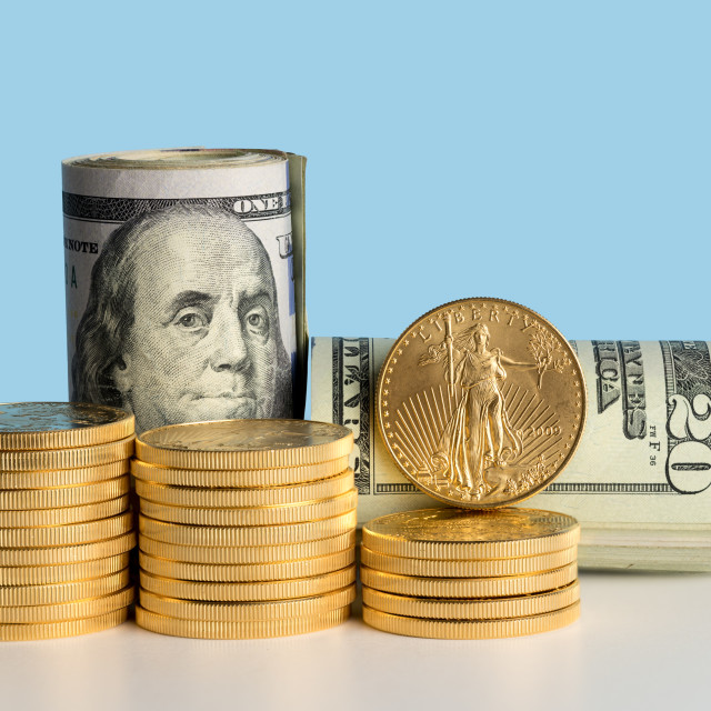 """""""Pure gold coins in front of bank rolls of US currency"""" stock image"""