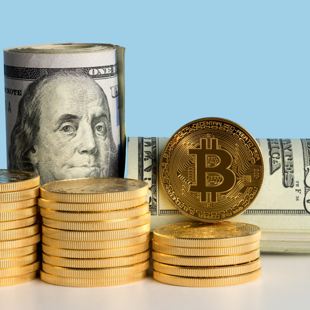 """""""Bitcoin coins in front of bank rolls of US currency"""" stock image"""