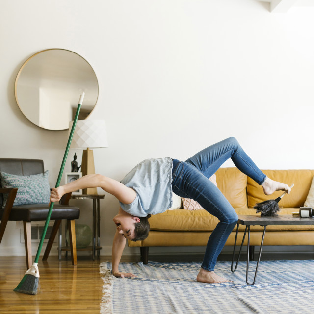 """Woman bending over backwards sweeping and dusting"" stock image"