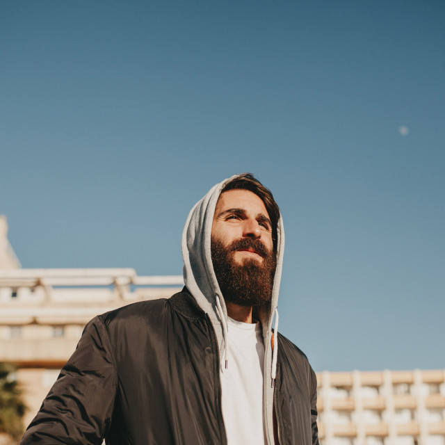 """""""Portrait of bearded and hooded man, with casual clothes, outdoor"""" stock image"""
