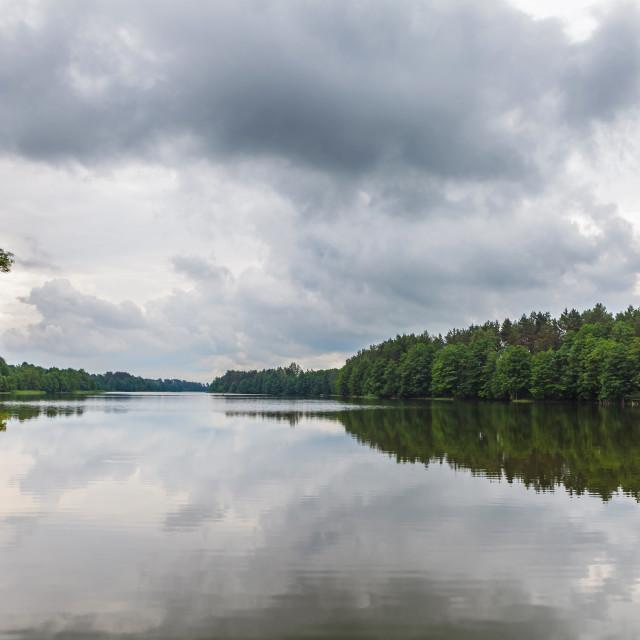"""Cloudy sky over calm lake"" stock image"