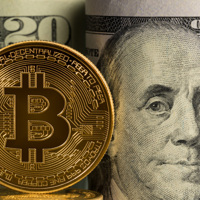 """""""Bitcoin coin in front of bank rolls of US currency"""" stock image"""