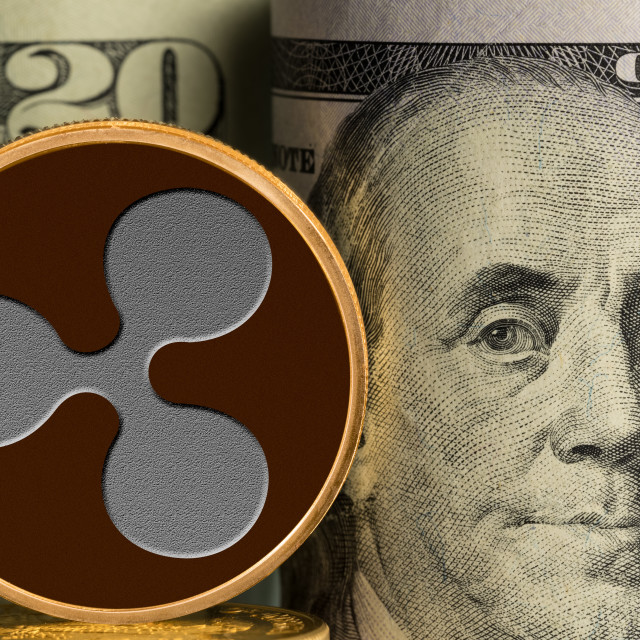 """""""Single Ripple coin in front of bank rolls of US currency"""" stock image"""