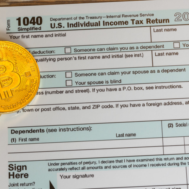 """""""Form 1040 Simplified with bitcoin coins for reporting currency gains"""" stock image"""