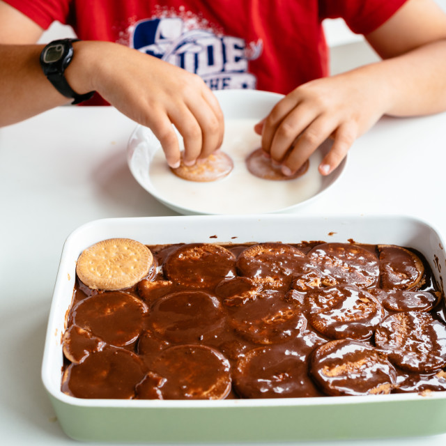 """Close up of child preparing homemade chocolate cake"" stock image"