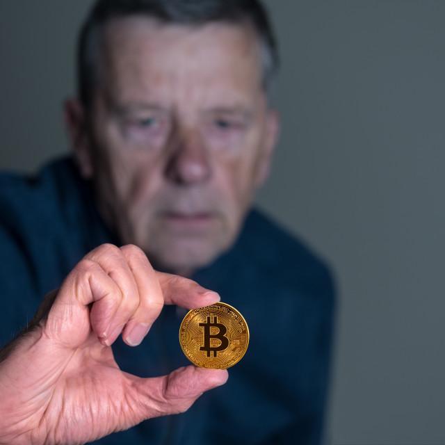 """Senior man holding a bitcoin at arms length"" stock image"