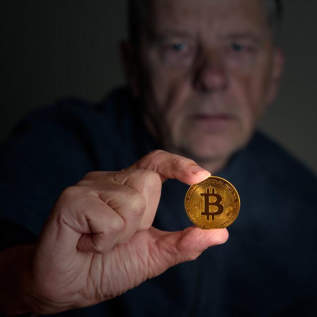 """Senior man examining a bitcoin at arms length"" stock image"