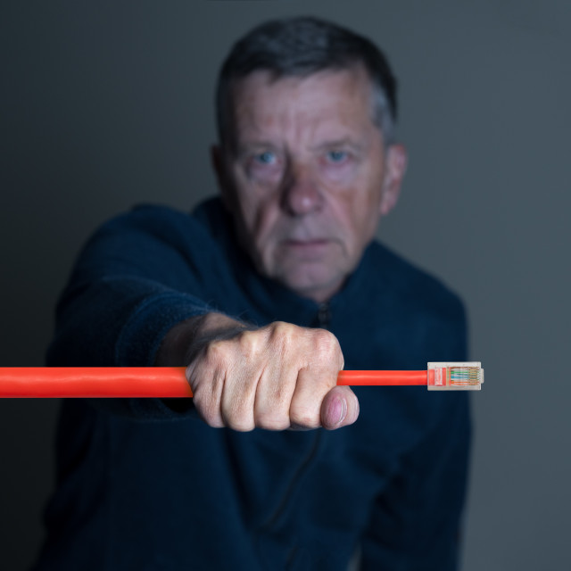 """""""Senior man squeezing ethernet cable to illustrate net neutrality"""" stock image"""