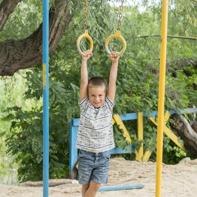 """""""A little boy is doing phisical exercises on a Sportsground"""" stock image"""