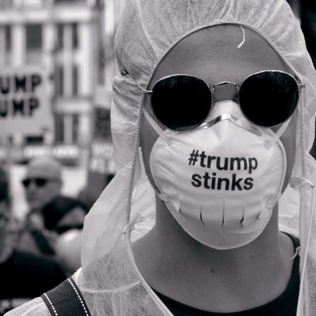 """Masked protestor attends the Donald Trump visit protests in London, UK"" stock image"