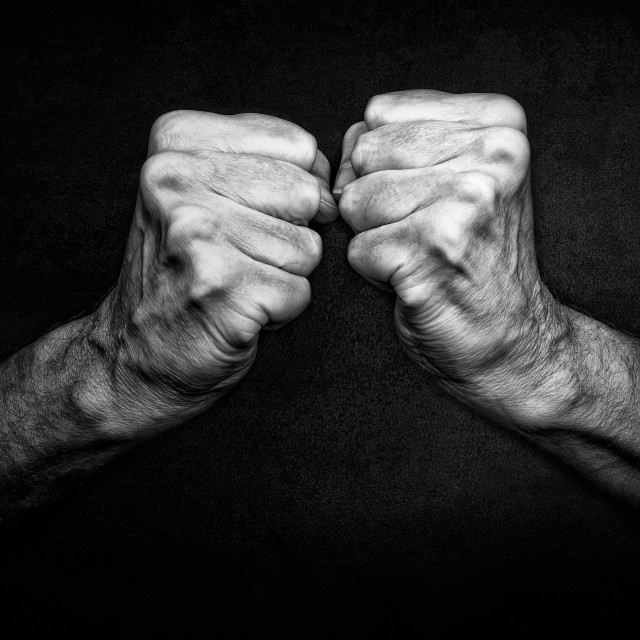 """Man's fists on dark"" stock image"