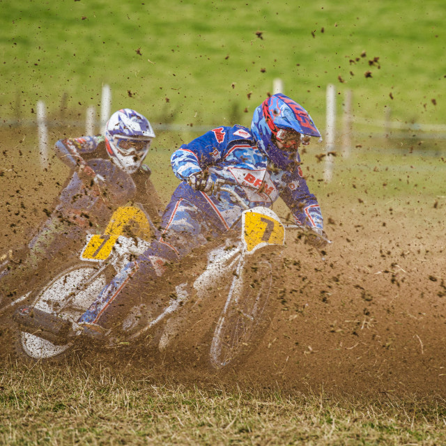 """Two motorbike riders racing on a grass track"" stock image"