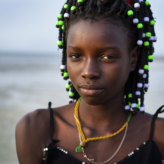 """Orango Island, Guinea-Bissau - February 2, 2018: Portrait of a beautiful young girl at the beach in the island of Orango at sunset."" stock image"