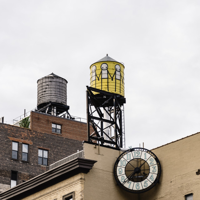 """Low angle view of water towers and clock against sky in New York"" stock image"