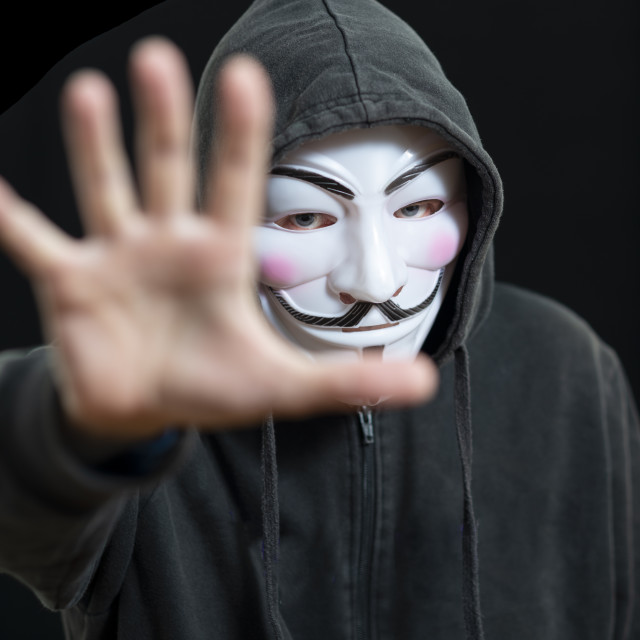 """Anonymous hacker wearing a Guy Fawkes mask and a black hoodie"" stock image"