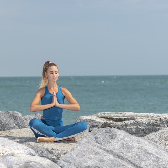 """woman sitting on the rocks by the sea meditating and practicing yoga"" stock image"