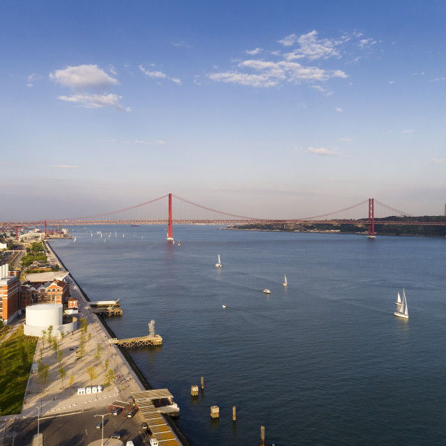 """Lisbon, Portugal - June 23, 2018: Aerial view of the city of Lisbon with sail boats on the Tagus River (Rio Tejo) and the 25 of April Bridge on the background;"" stock image"