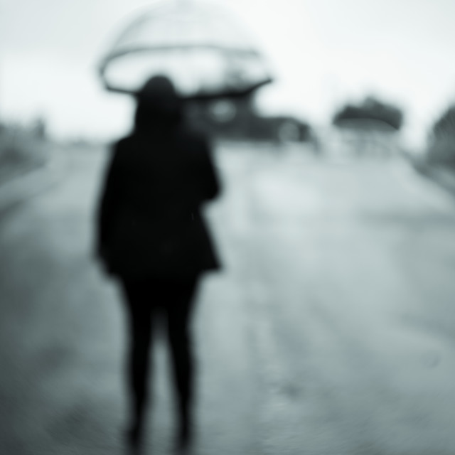 """Woman with unfocused backs with transparent umbrella in the rain"" stock image"