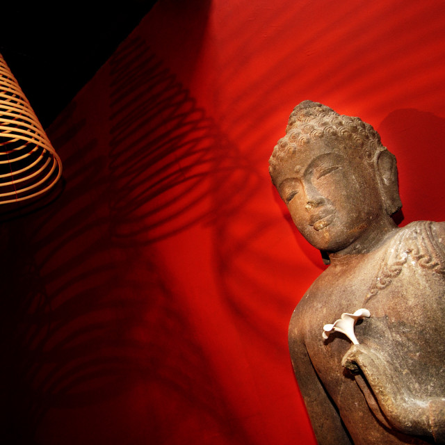 """Statue of Buddha Against Red Wall"" stock image"