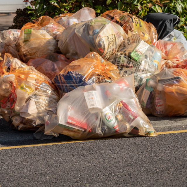 """Recycling plastic waste sacks in a pile awaiting collection"" stock image"
