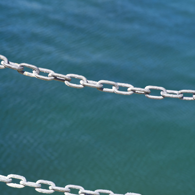 """""""In focus chain and out of focus sea"""" stock image"""