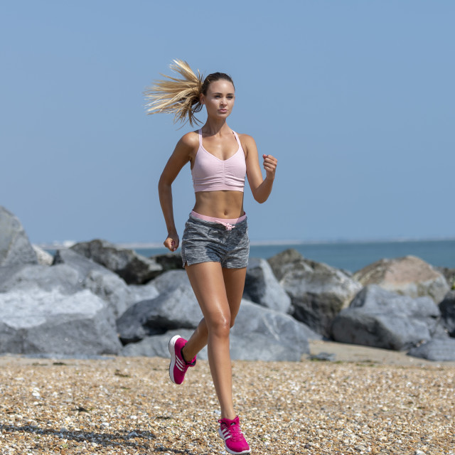 """fit woman running along a beach"" stock image"