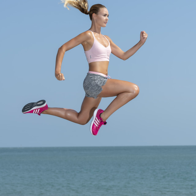 """Fit woman running and jumping across rocks, keeping fit outside"" stock image"