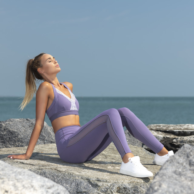 """attractive sporty woman sitting resting enjoying the sun by the sea, getting a tan."" stock image"