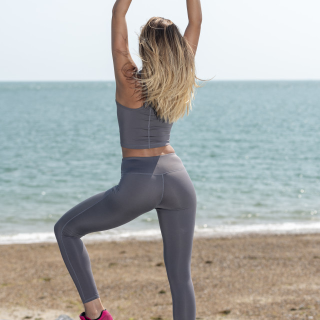 """fit sporty woman stretching her arms, warming up exercises outside by the sea, back view"" stock image"
